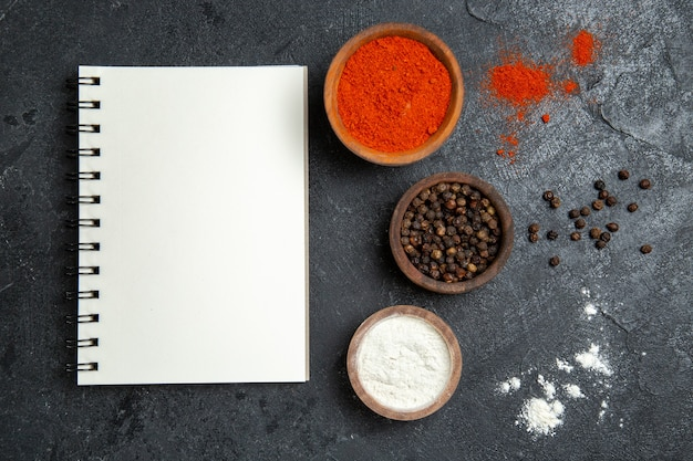 Vista superior de diferentes condimentos pimienta dentro de macetas en espacio gris
