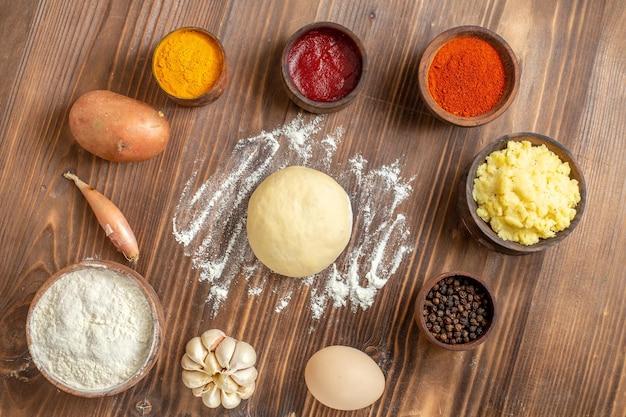 Vista superior de diferentes condimentos con puré de patatas y ajo en el escritorio de madera marrón pimiento picante comida de patata madura
