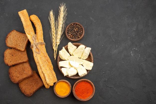 Vista superior de diferentes condimentos con queso y hogazas de pan negro sobre negro