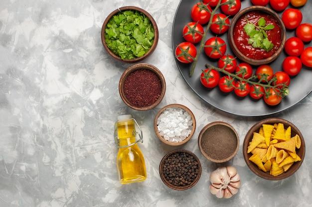 Vista superior de diferentes condimentos con tomates cherry y aceite en el escritorio blanco
