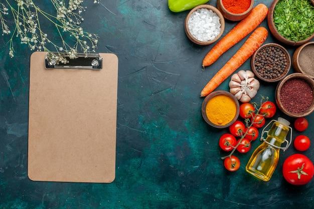 Vista superior de diferentes condimentos con tomates frescos sobre fondo verde oscuro ingrediente producto comida comida vegetal