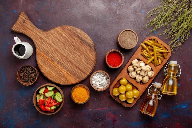Vista superior de diferentes condimentos con verduras y aceite en una superficie oscura.