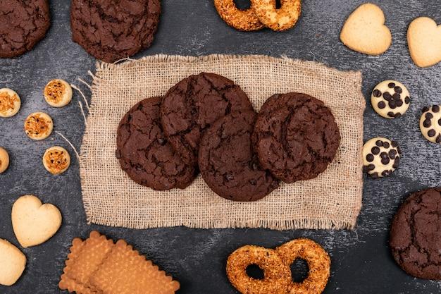 Vista superior de diferentes cookies en cilicio sobre superficie oscura