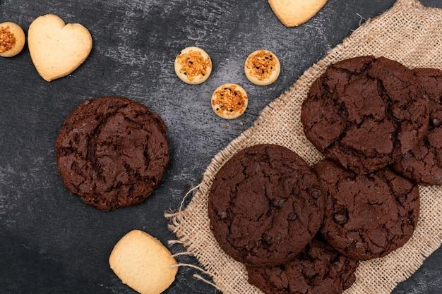 Vista superior, diferentes cookies en superficie oscura