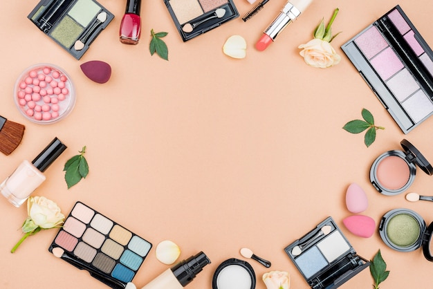 Vista superior de diferentes cosméticos con espacio de copia sobre fondo beige