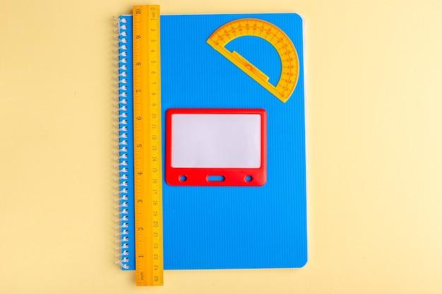 Vista superior de diferentes cuadernos azul con regla sobre superficie amarilla clara