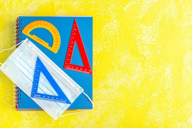 Vista superior de diferentes figuras con cuadernos y máscara en la superficie amarilla
