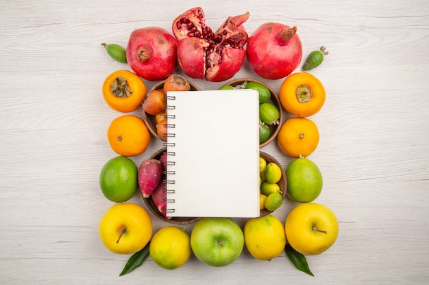 Vista superior de diferentes frutas de composición de frutas frescas con bloc de notas sobre fondo blanco.