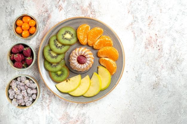 Vista superior de diferentes frutas composición frutas frescas y en rodajas con pastel sobre fondo blanco frutas suaves salud vitamina madura