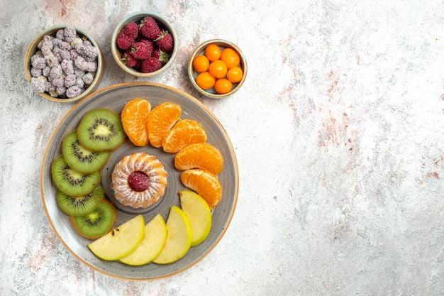 Vista superior de diferentes frutas composición frutas frescas y en rodajas con pastel sobre fondo blanco frutas suaves vitamina madura salud