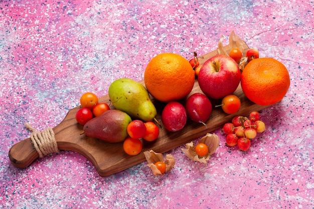 Vista superior de diferentes frutas de composición de frutas frescas y suaves sobre fondo rosa.