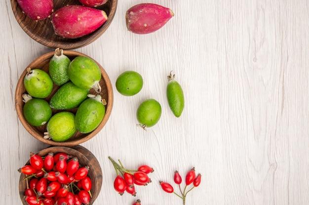 Vista superior de diferentes frutas frescas dentro de placas sobre fondo blanco exótica dieta madura color vida saludable tropical