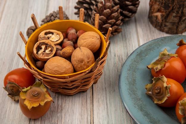 Vista superior de diferentes frutos secos en un balde con caquis frescos suaves en un plato sobre una pared de madera gris