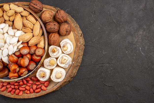 Vista superior de diferentes frutos secos con confituras blancas sobre superficie oscura