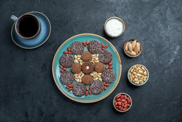 Vista superior de diferentes galletas a base de chocolate con nueces y una taza de café en la superficie gris caramelo bombón azúcar dulce pastel de galletas