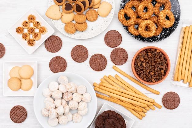 Vista superior diferentes galletas granos de café y palitos de pan en la mesa blanca