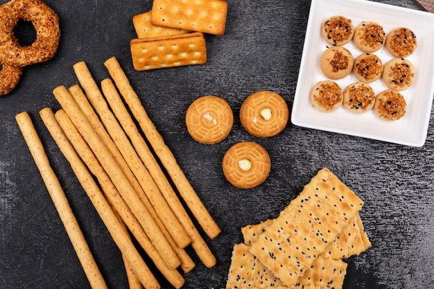 Vista superior de diferentes galletas y palitos de pan en la superficie oscura