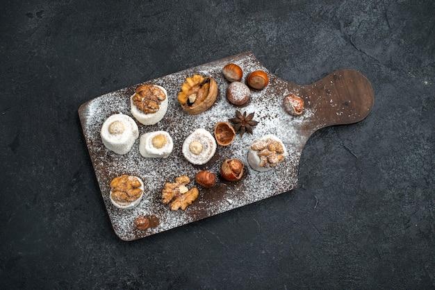 Vista superior de diferentes galletas con pasteles y nueces en la superficie gris oscuro