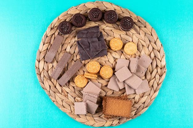 Vista superior diferentes galletas waffles y chocolate sobre superficie azul