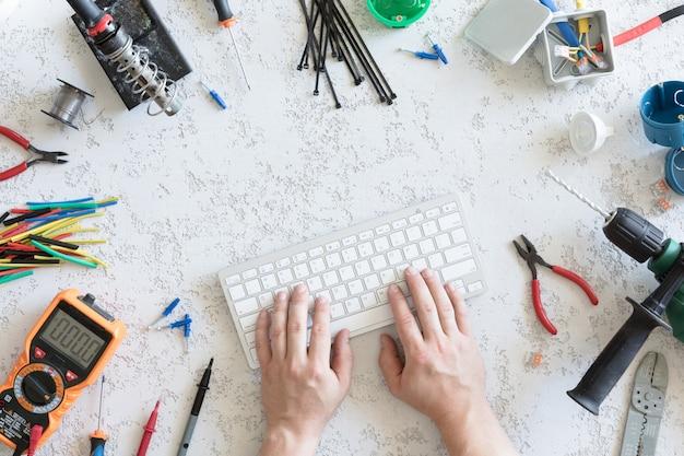 Vista superior de diferentes herramientas eléctricas, mano del hombre en el teclado de la computadora, endecha plana. herramientas para un electricista, voltajes y mediciones de corriente.