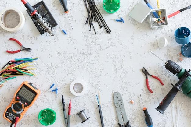 Vista superior de diferentes herramientas eléctricas sobre fondo de hormigón blanco, endecha plana. herramientas para un electricista, voltajes y mediciones de corriente.