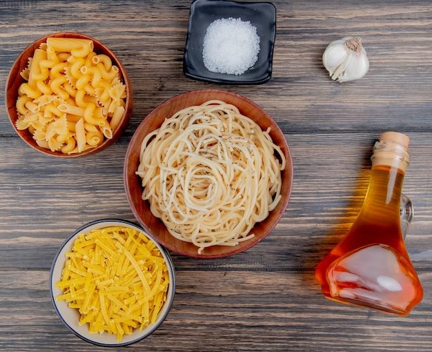 Vista superior de diferentes macarrones como tallarines de espagueti y otros con sal, ajo, mantequilla derretida sobre madera