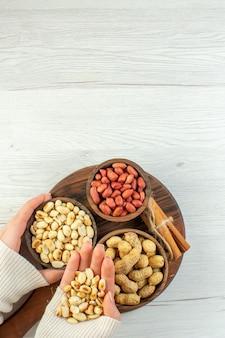 Vista superior diferentes nueces cacahuetes avellanas y nueces en mesa de madera blanca