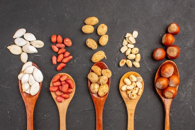 Vista superior de diferentes nueces cacahuetes frescos y otras nueces en cucharas sobre superficie oscura