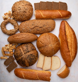 Vista superior de diferentes panes como baguette de bagel de mazorca blanco y centeno sobre fondo blanco.