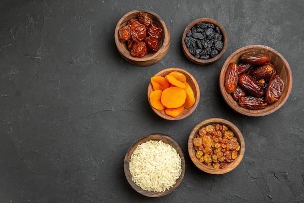 Vista superior diferentes pasas con khurma en pasas de frutos secos de superficie gris