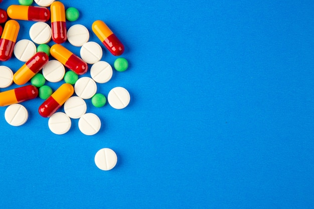 Vista superior de diferentes pastillas sobre fondo azul.