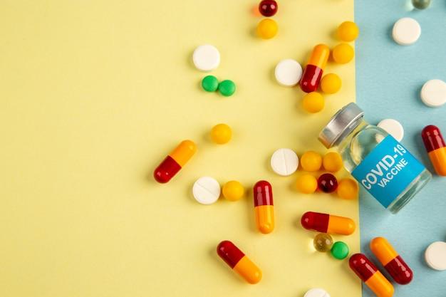 Vista superior de diferentes píldoras con vacuna sobre fondo amarillo-azul