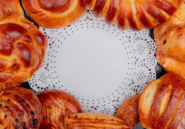 Vista superior de diferentes productos de panadería en forma redonda alrededor de papel tapete como fondo