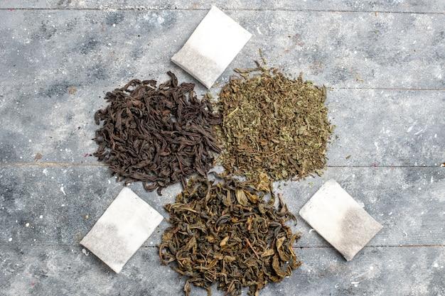Vista superior de diferentes sabores secos de té fresco en el escritorio gris
