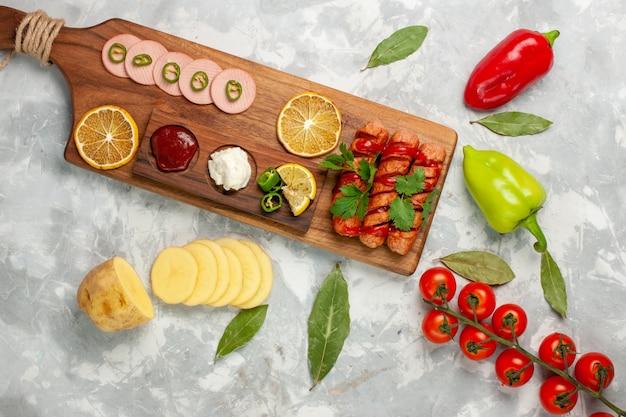 Vista superior de diferentes salchichas de composición de alimentos con tomates frescos y limones en la comida de escritorio de color blanco claro, comida, color veegtable
