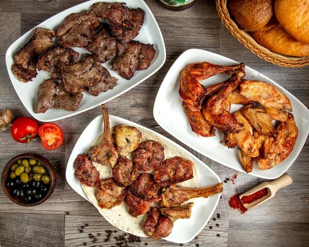 Vista superior de diferentes tipos de kebabas de ternera con pollo y costillas de cordero en una mesa de madera