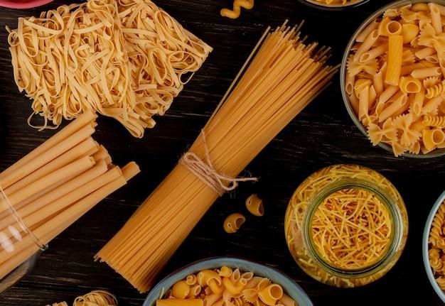 Vista superior de diferentes tipos de pastas como tallarines de espagueti bucatini y otros tallarines sobre superficie de madera