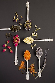 Vista superior de diferentes variedades de té en las cucharas de plata sobre la superficie negra