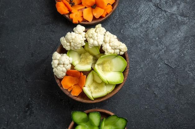 Vista superior de diferentes vegetales diseñados dentro de macetas en escritorio gris