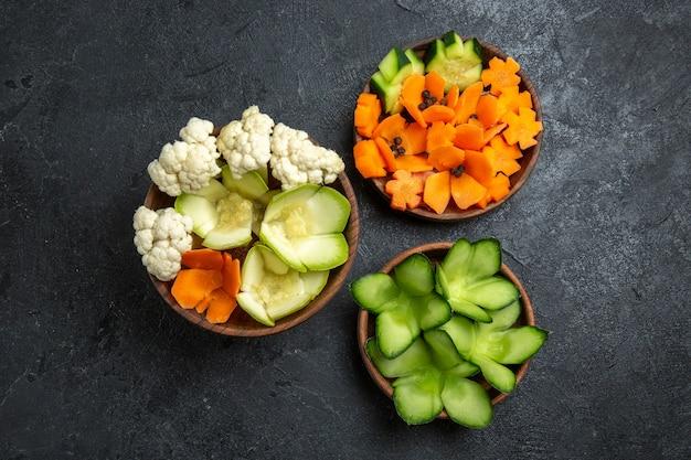 Vista superior de diferentes vegetales diseñados dentro de macetas en un espacio gris