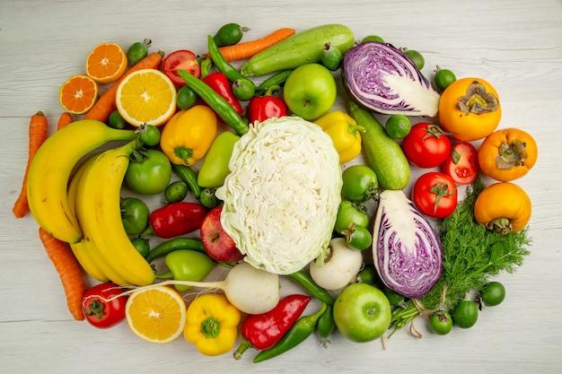 Vista superior de diferentes verduras con frutas frescas sobre fondo blanco claro, ensalada, comida, salud, color, dieta madura