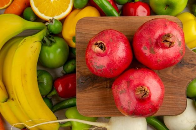 Vista superior de diferentes verduras con frutas frescas sobre fondo blanco, dieta, alimentos, salud, ensalada de color maduro