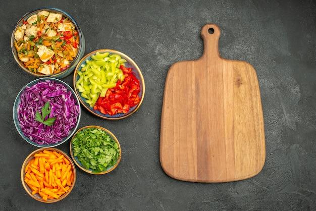 Vista superior de diferentes verduras en rodajas con ensalada de pollo en la dieta de ensalada de salud de escritorio oscuro