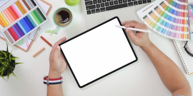 Vista superior del diseñador gráfico masculino en tableta de pantalla en blanco