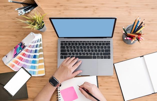 Vista superior del diseñador usando la computadora portátil en el escritorio en la oficina