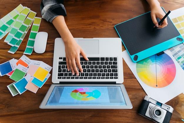 Vista superior de diseñadora gráfica con tableta y portátil