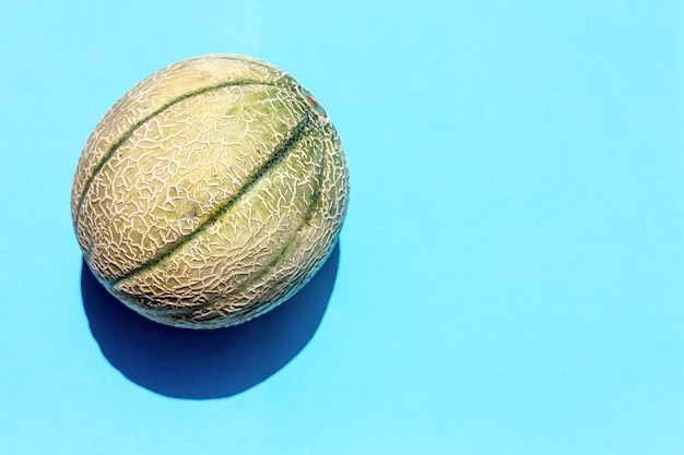 Vista superior del diseño creativo de melón amarillo de verano. melón maduro dulce en azul