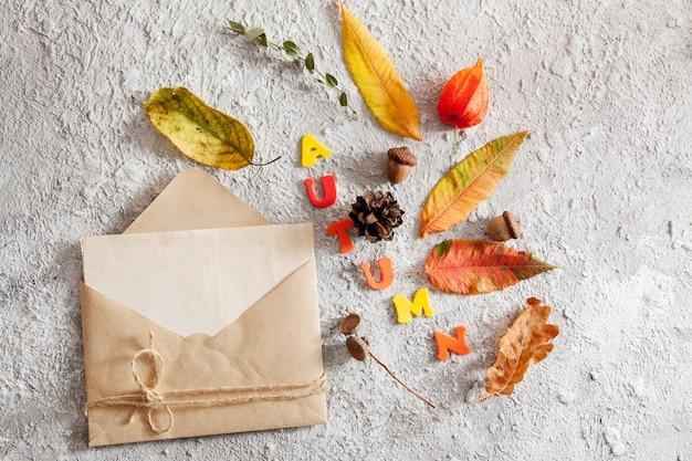 Vista superior del diseño con la palabra otoño, maqueta de sobres y hojas caídas. concepto de otoño