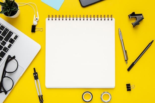 Vista superior disposición de papelería sobre fondo amarillo con bloc de notas vacío