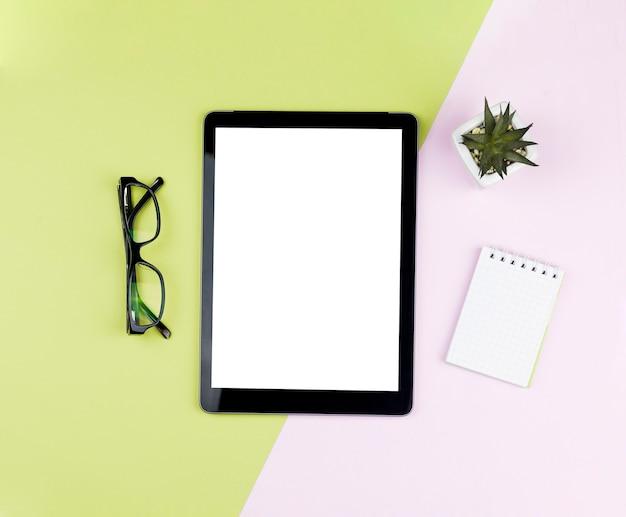 Vista superior disposición de papelería sobre fondo azul con maqueta de tableta